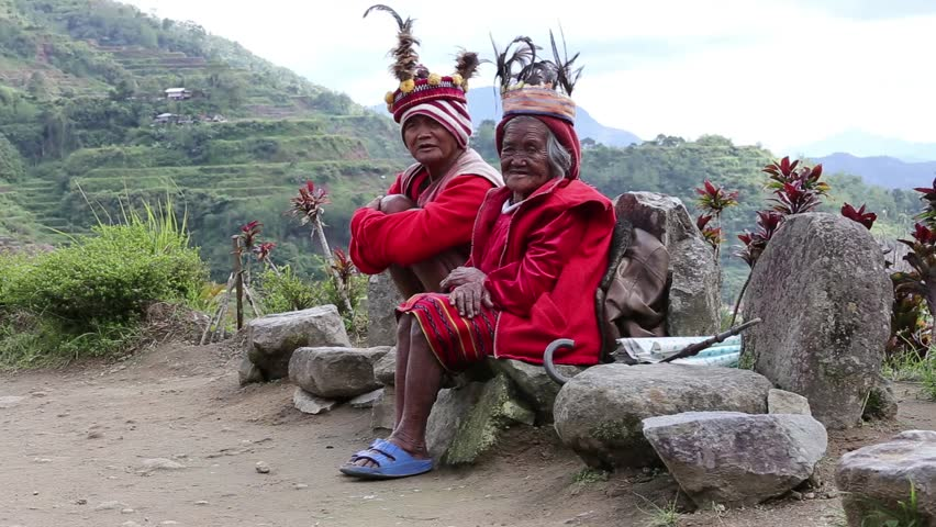 BANAUE, PHILIPPINES - JANUARY 24, 2014 : Unknown old ifugao people in national dress next to rice terraces. Ifugao - the people in the Philippines. Refers to the mountain peoples.
