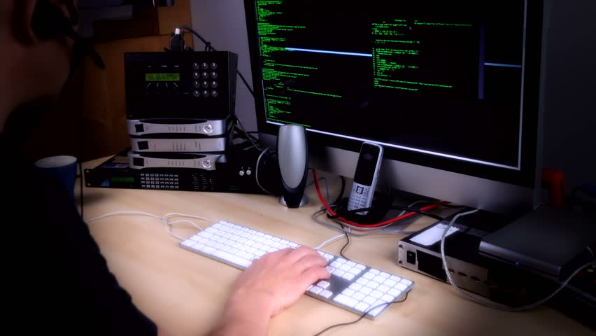 A computer programmer or hacker busy at work at night surrounded by streaming code on screen, ISDN and broadband connections and disk drives and wires.