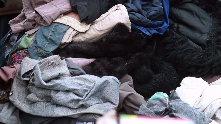 Clothes pile for poor people winter outdoor, male choosing coat