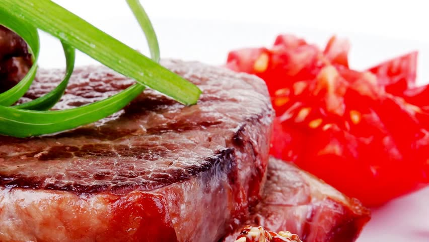 grilled meat beef steaks strips plate with sweet pea and tomatoes 1920x1080 intro motion slow hidef hd - HD stock video clip