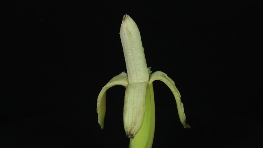 Peeled banana rotates on a black background  loop  - HD stock video clip
