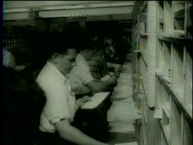 Post workers sort mail at the U.S. Postal Service processing center, USA, circa 1958 - MGM PICTURES, UNIVERSAL-INTERNATIONAL NEWSREEL, USA, filmed in 1958