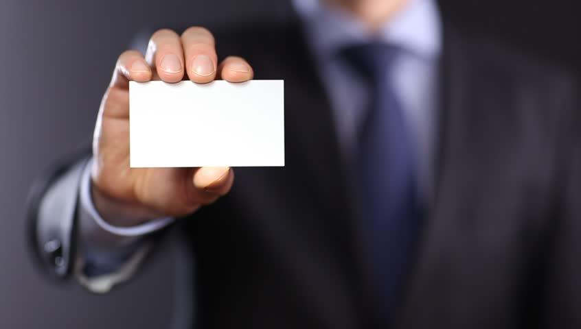 Man's hand showing business card - closeup shot on dark background