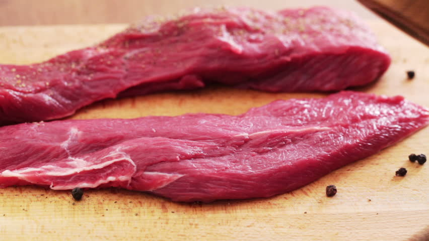 HD 1080 static: beef cutlets are seasoned with black pepper, using small pepper grinder;
