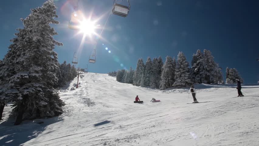 Sunny day in the snowy mountain and ski lift moves up with skiers.Skiers  enjoying with the day.Sun was shining over the skiers.Kids are  laying down on the snow and watchin snowboarders.Just heaven. - HD stock footage clip