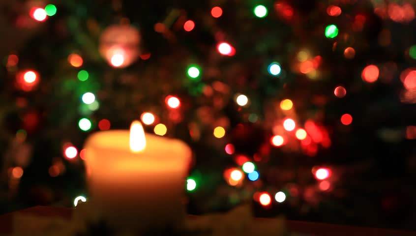 Christmas Decoration. Burning candle on blinking lights background