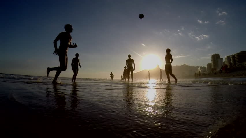 Silhouettes of Carioca Brazilians playing beach football at sunset on Ipanema Beach Rio de Janeiro Brazil silhouetted slow motion #5731385