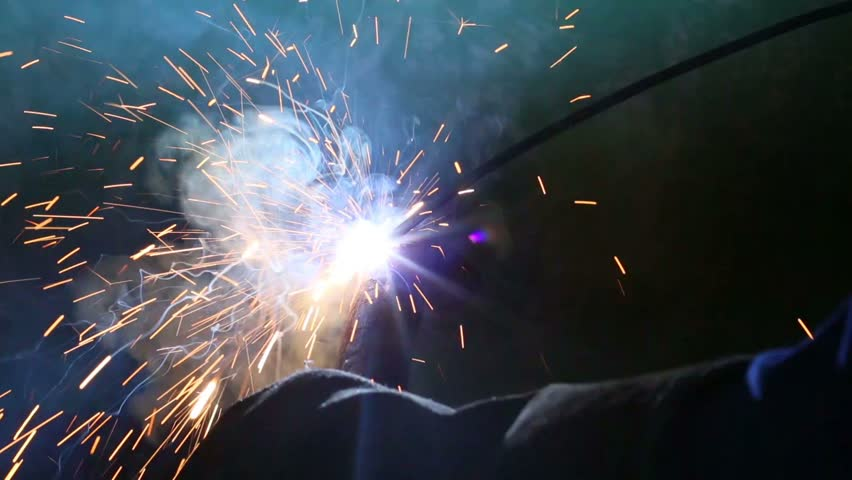 Flashes and lot of sparks from welding work at construction site in dark - HD stock footage clip