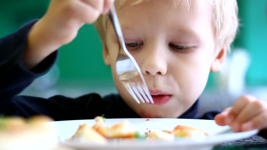 closeup of little cute boy eating pizza. Sequence