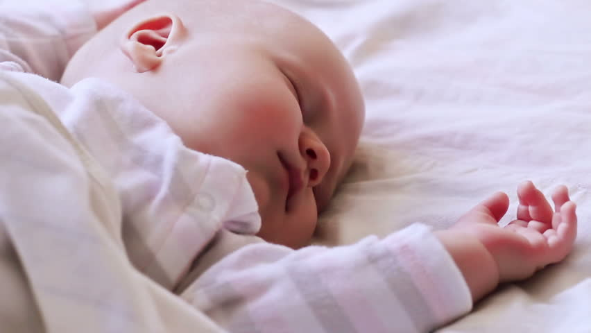 Close-up portrait of a beautiful sleeping baby in white blanket - HD stock footage clip