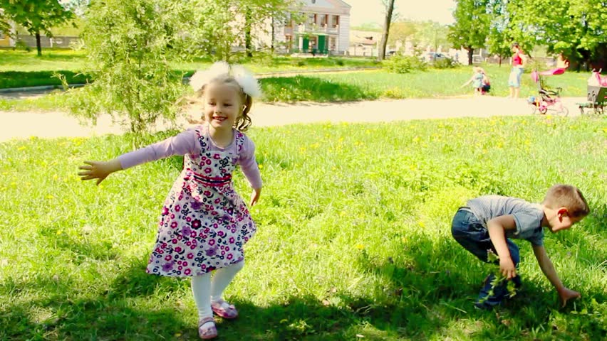 Boy And Girl Are Playing Outside And Falling Down In Grass
