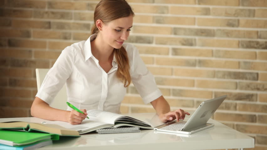 Happy Girl Sitting At Desk Writing In Workbook Using