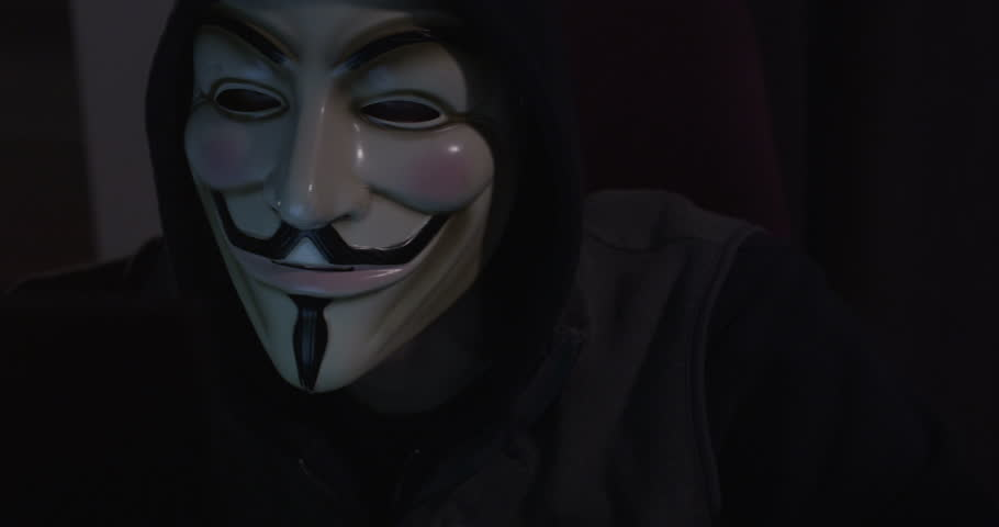 NEW YORK, NY, USA - CIRCA 2013: A hacker activist sits at their laptop computer in a grungy apartment. They are wearing a Guy Fawkes mask which has become an iconic symbol of online social movements | Shutterstock HD Video #5769365