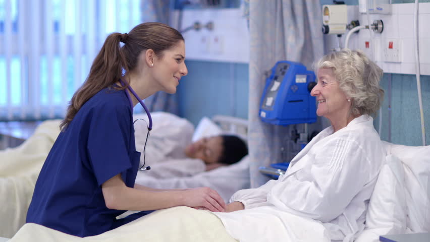Caring nurse chats with an elderly female patient on a hospital ward. | Shutterstock HD Video #5784089