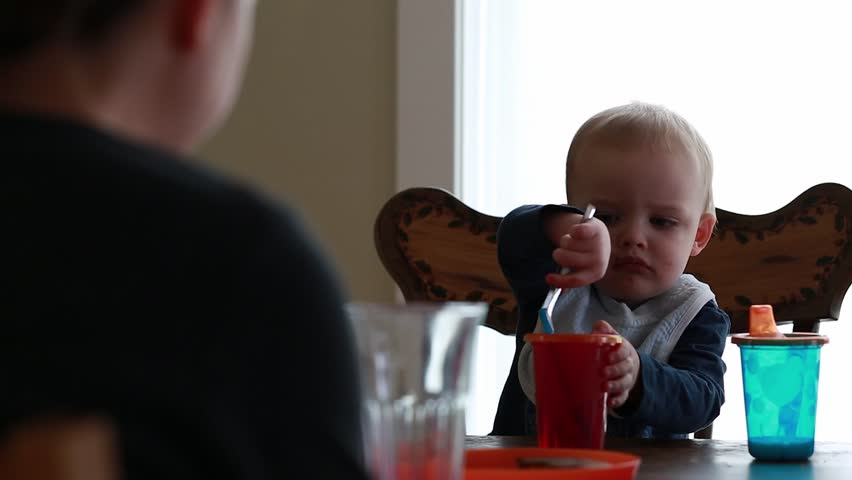A toddler eating his breakfast with his mother at the table | Shutterstock HD Video #5795150