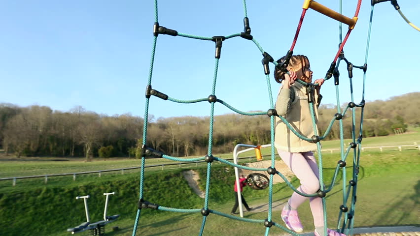 Roaming shot of a young girl climbing up a rope climbing frame on a sunny day - HD stock footage clip