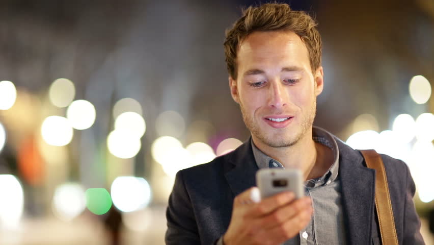 Man sms texting using app on smart phone at night in city. Handsome young business man using smartphone smiling happy wearing suit jacket outdoors. Urban male professional in his 20s.