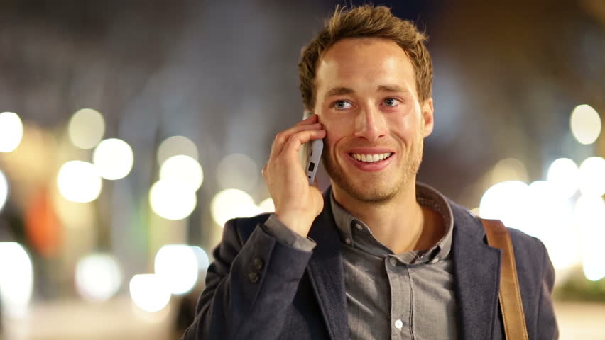 Smart phone man calling on mobile phone at night in city. Handsome young business man talking on smartphone smiling happy wearing suit jacket outdoors. Urban male professional in his 20s. - HD stock footage clip