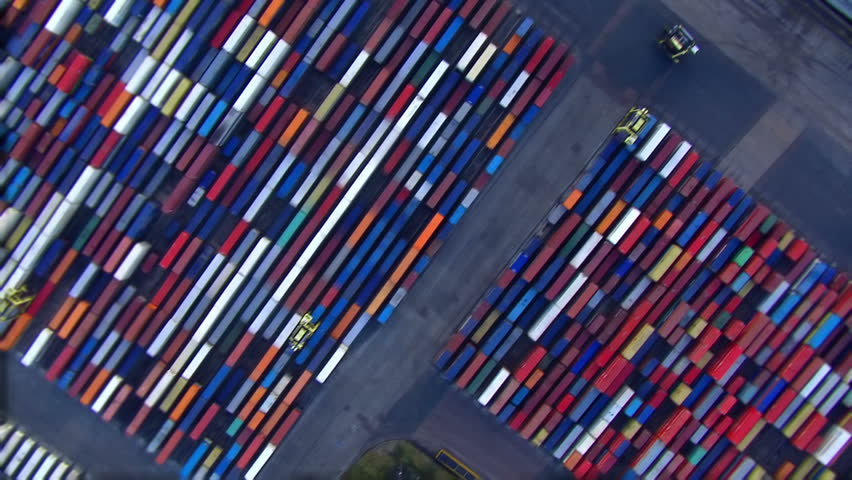 Aerial view of cranes moving amongst containers at a busy London port - HD stock footage clip