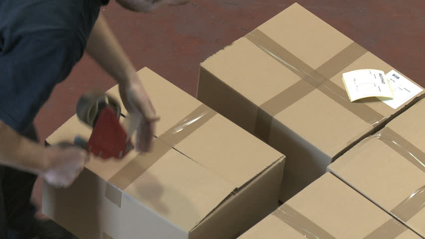 Top view of an employee closes cardboard boxes of merchandise for shipment to international destinations