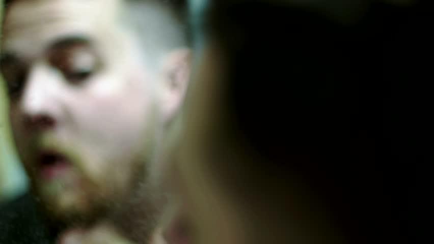 A man grooming himself in a mirror.