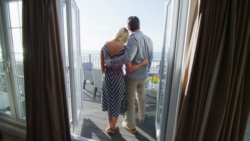 Romantic couple in love go to look at the view from the balcony of their beachside apartment.