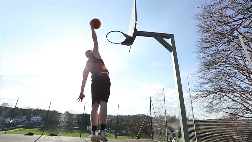 Basketball player slam dunking the ball on an outdoor court in slow motion - HD stock video clip