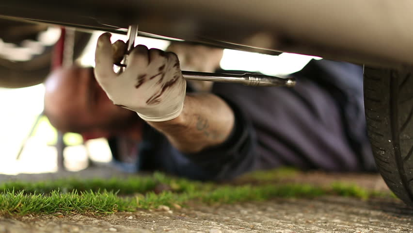 Car mechanic underneath a car unscrewing components from the under tray - HD stock footage clip