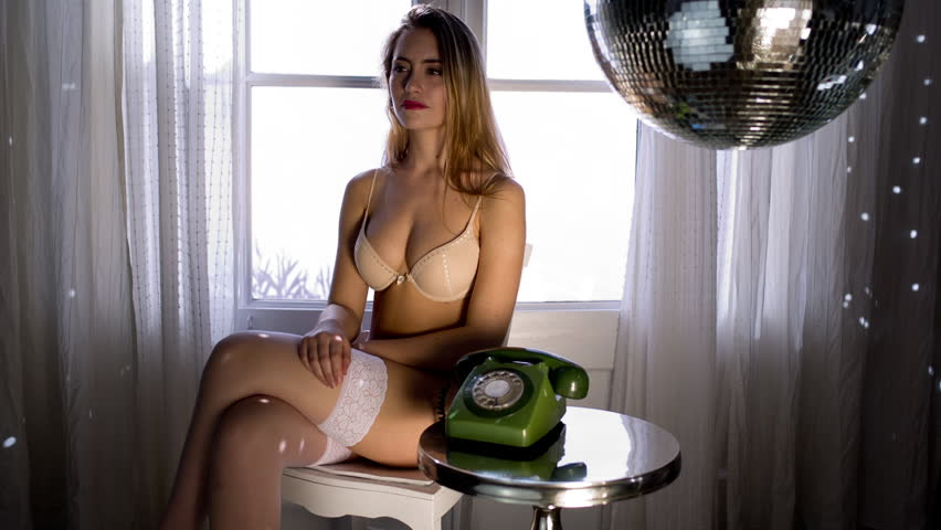 beautiful sexy woman poses and talks on telephone in lingerie in a lounge bathed in sunlight. Useful for fashion, lifestyle and health and beauty  - HD stock footage clip