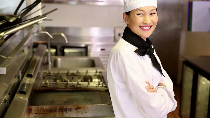 Happy chef smiling at camera beside the stove in commercial kitchen - HD stock video clip