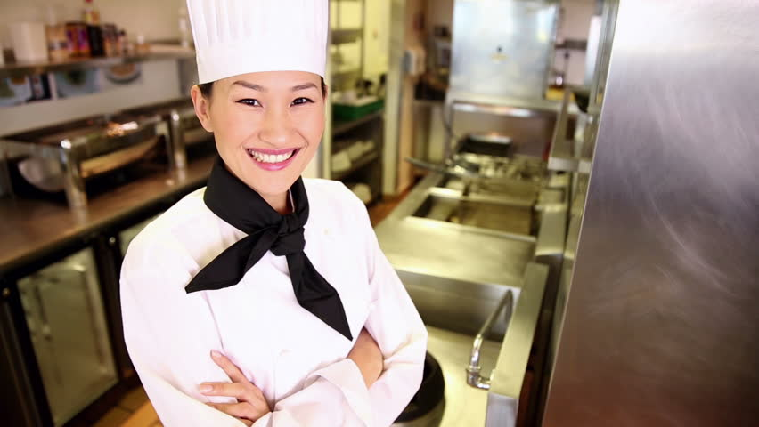 Happy chef smiling at camera in commercial kitchen - HD stock footage clip