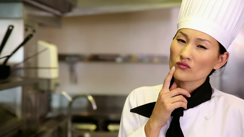 Thoughtful chef smiling at camera in commercial kitchen - HD stock footage clip