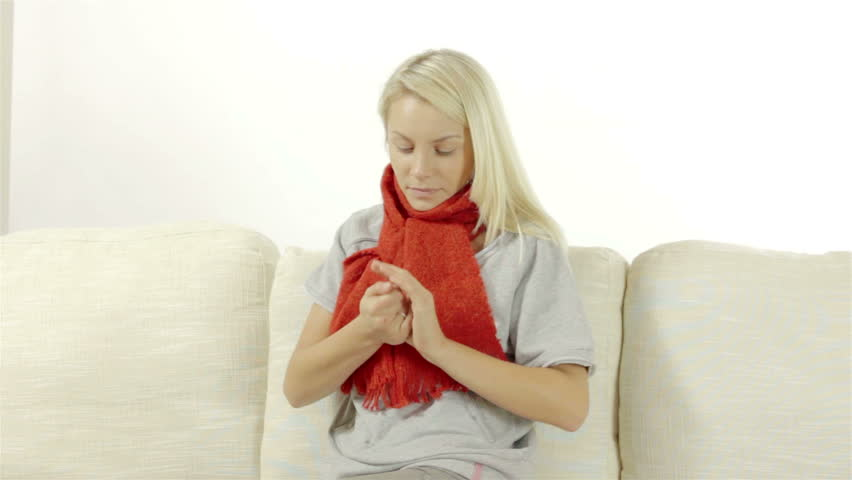 Sick young woman at home freezing