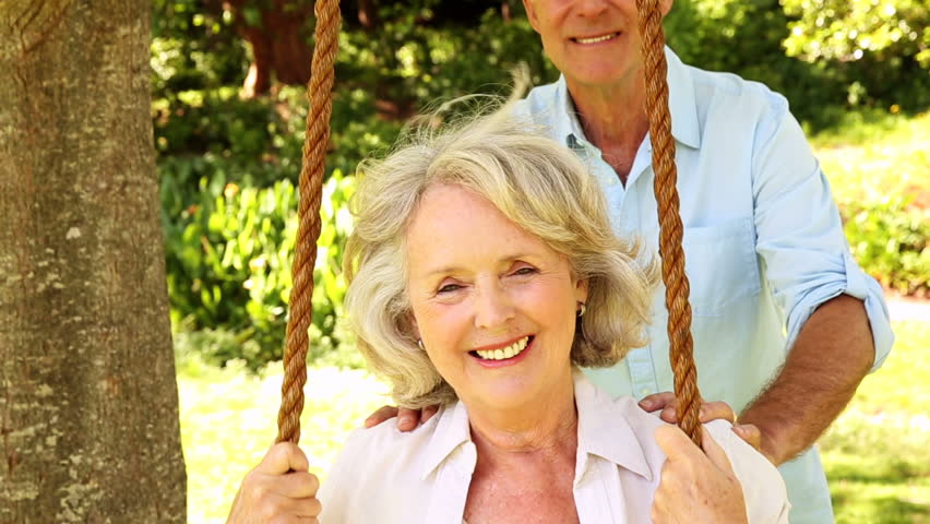 Retired man pushing his wife on swing on a sunny day - HD stock footage clip