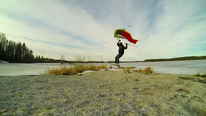 Kitewing skier jumping over a rock in slow motion - HD stock video clip