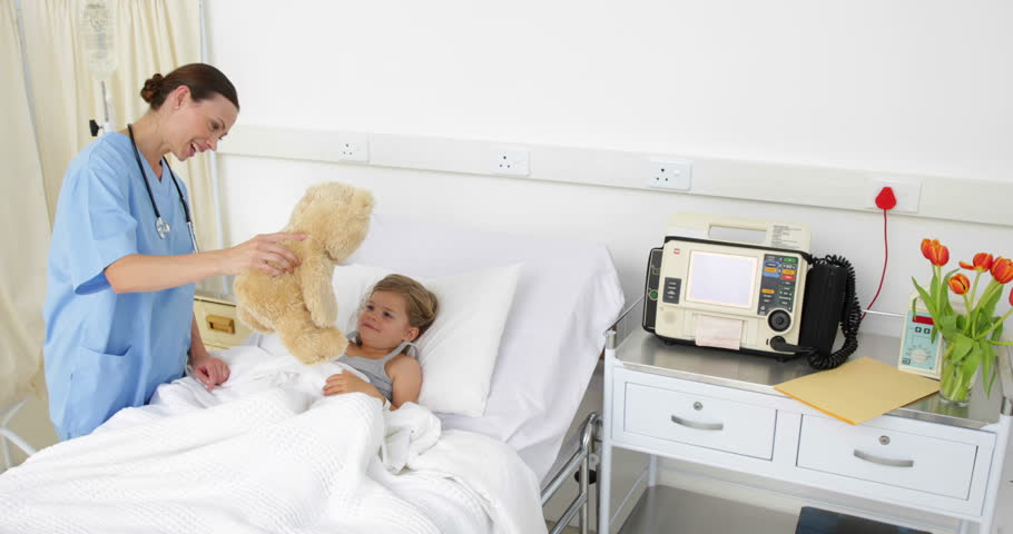 Nurse trying to cheer up a sick little girl at the hospital - 4K stock footage clip