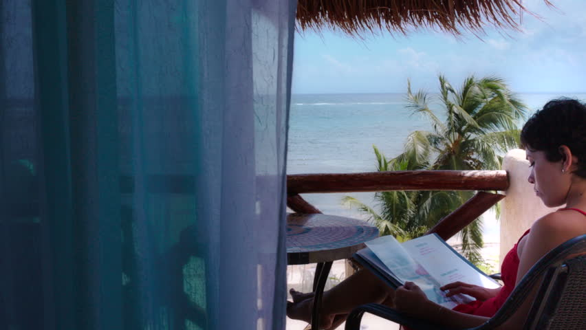Hispanic woman reading on a balcony at the caribbean - HD stock video clip