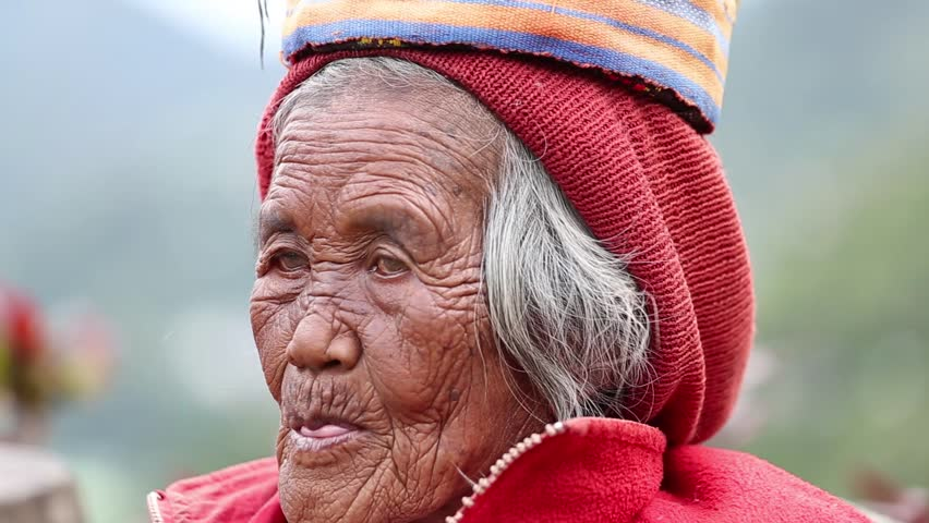 BANAUE, PHILIPPINES - JANUARY 24, 2014 : Unknown old ifugao woman in national dress next to rice terraces. Ifugao - the people in the Philippines. Refers to the mountain peoples.