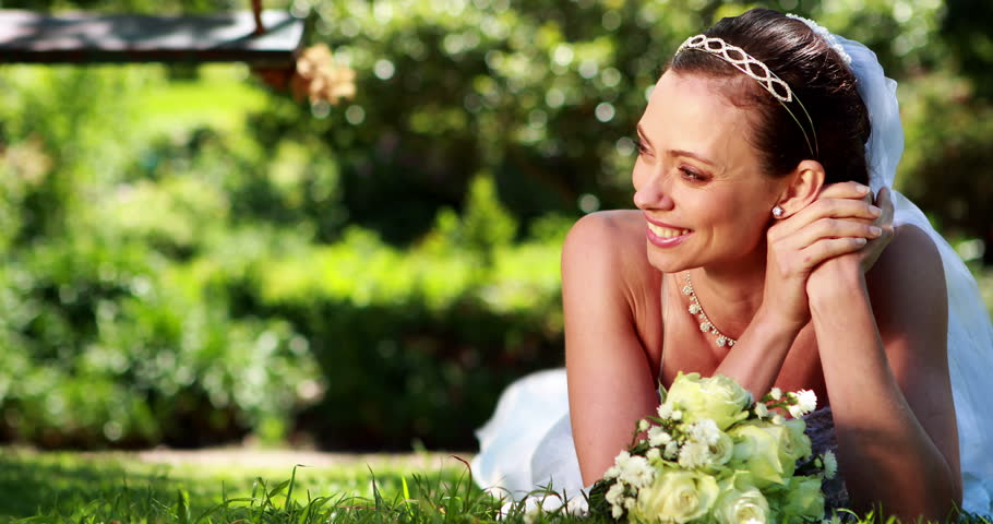 Beautiful bride smiling at camera lying on the grass on her wedding day - 4K stock video clip