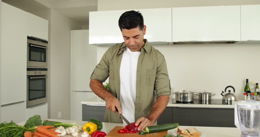 Handsome man chopping vegetables at home in the kitchen - 4K stock video clip
