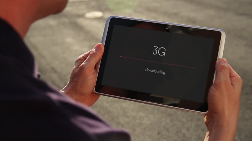 A man downloads a file over 3G on his handheld tablet. | Shutterstock HD Video #5960768