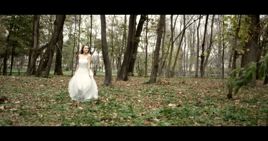 Beautiful bride in her wedding dress running in a park in slow motion