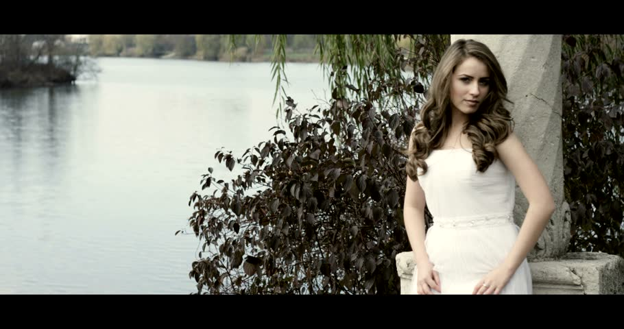 Beautiful bride in her wedding dress next to a lake