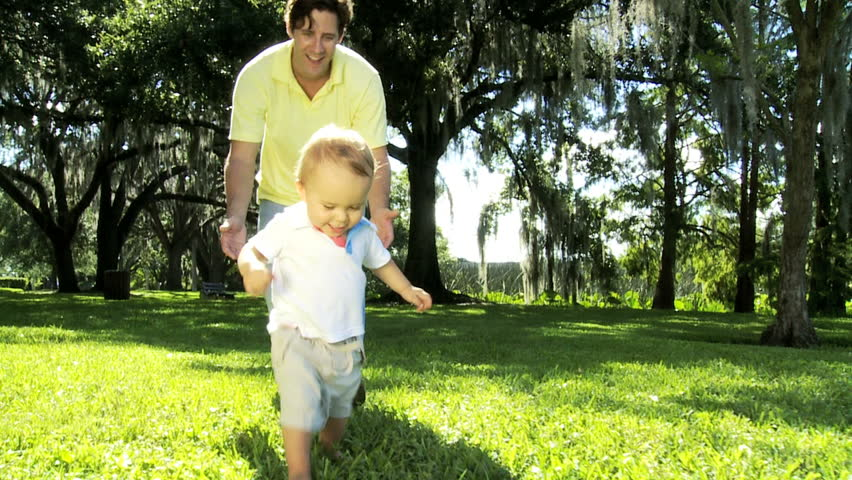 Proud young Caucasian father with his smiling little boy as he walks barefoot grass enjoying outing park - Proud Caucasian Father Baby Son Enjoying Outing Park - HD stock footage clip