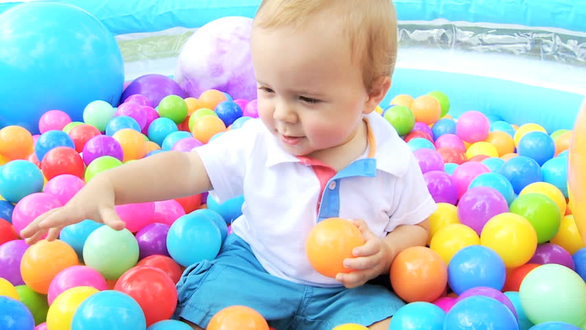 Smiling little caucasian boy playing in paddling pool full for Baby garden pool