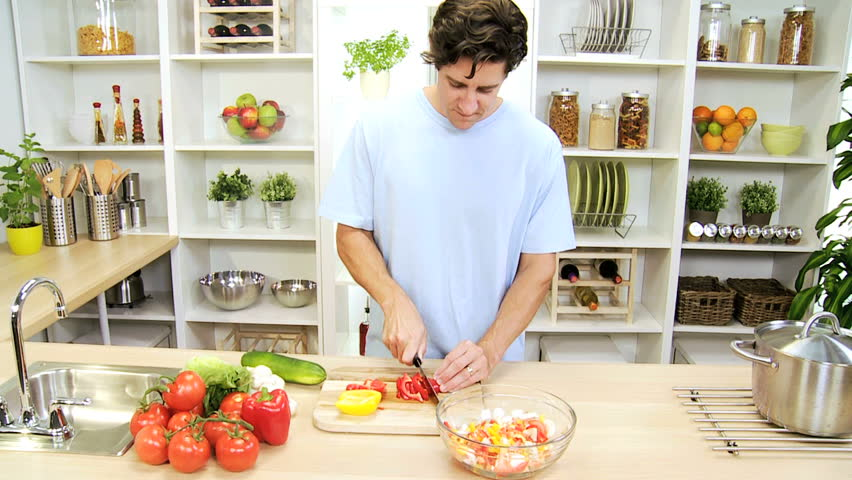 Healthy young Caucasian male home kitchen preparing tasty nutritious fresh vegetables low calorie meal - Healthy Caucasian Man Slicing Fresh Vegetables - HD stock video clip