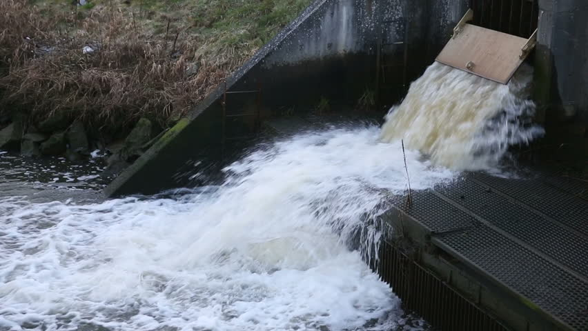 Storm Drain Run Off. Water pouring out of a flood gate at a pumping station.