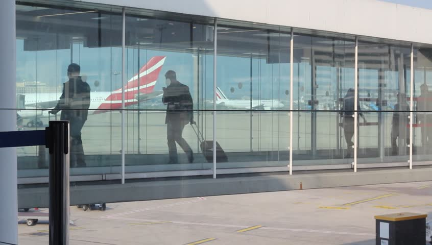 Unrecognizable people walking by jetty from the airplane to the airport - airport Charles de Gaulle, Paris, France