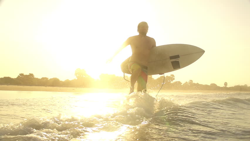 SLOW MOTION: Surfer goes surfing at sunset