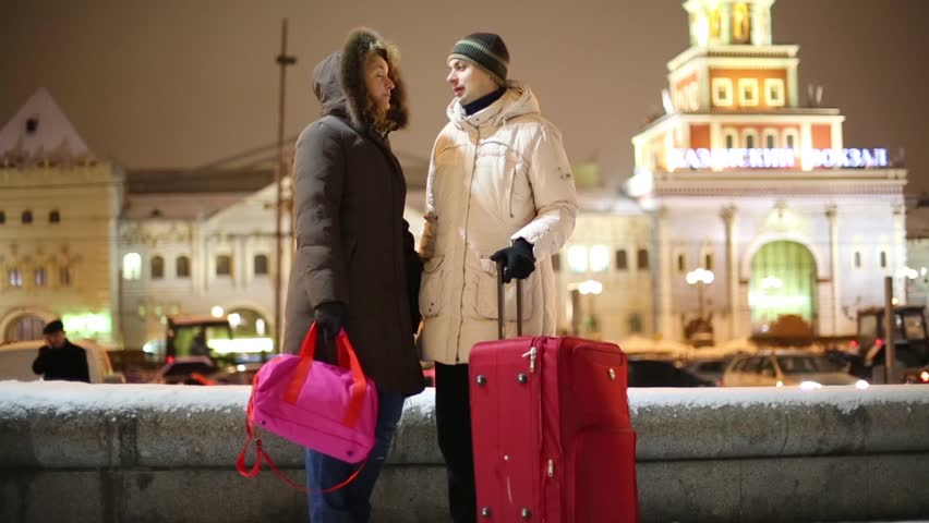 Man and woman stand with big bag, talk and look at watch near Kazansky railway station at winter night